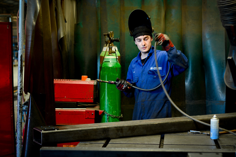Apprentice with welding torch