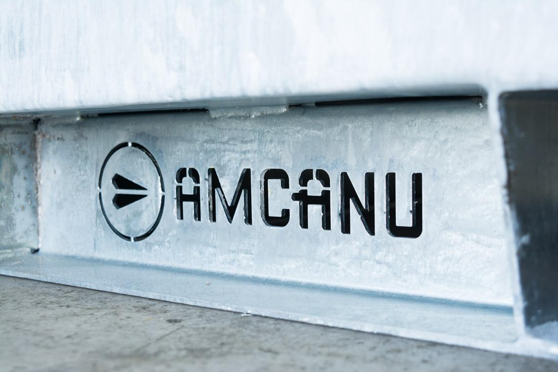 Amcanu logo cut out of metal in enclosure