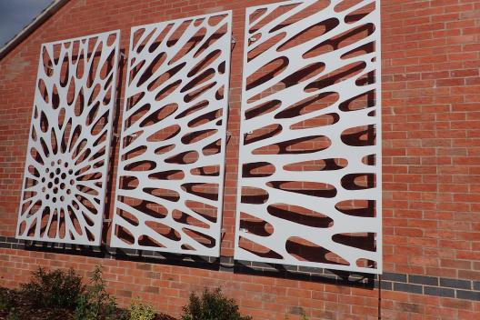 Metal powder-coated sculpture attached to a wall.